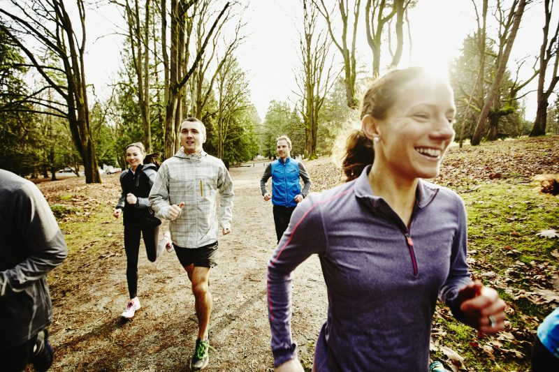 Female runner leading group of friends on trail